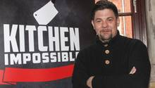 """Starkoch Tim Mälzer vor einem Plakat von """"Kitchen Impossible"""""""