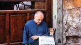 Ein Hund liest gemeinsam mit einem Mann die Tageszeitung
