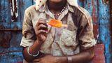 Ein junger Mann mit einer Ratte auf der Schulter isst ein Wassereis