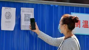 China, Wuhan: Eine Anwohnerin scannt einen Gesundheits-QR-Code am Eingang zu ihrer Gemeinde im Stadtbezirk Wuchang