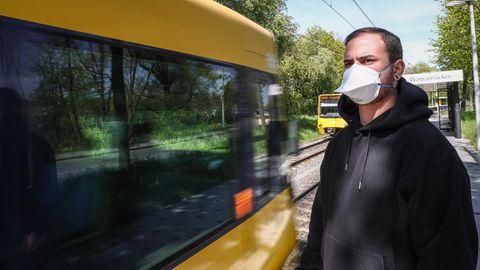 Ein junger Mann trägt vor einer einfahrenden Stadtbahn eine Atemschutzmaske