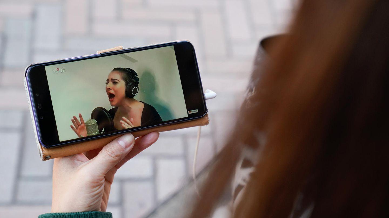 Die Japanerin Noemi sieht auf ihrem Smartphone die Live-Stream-Performance von Lady Gaga.