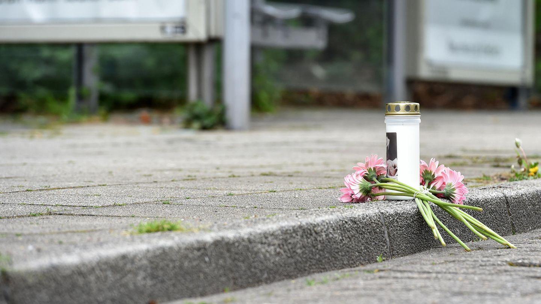 Eine Kerze und Blumen liegen an einer Haltestelle an der in der Nacht ein 14 Jahre alter Junge erstochen wurde.