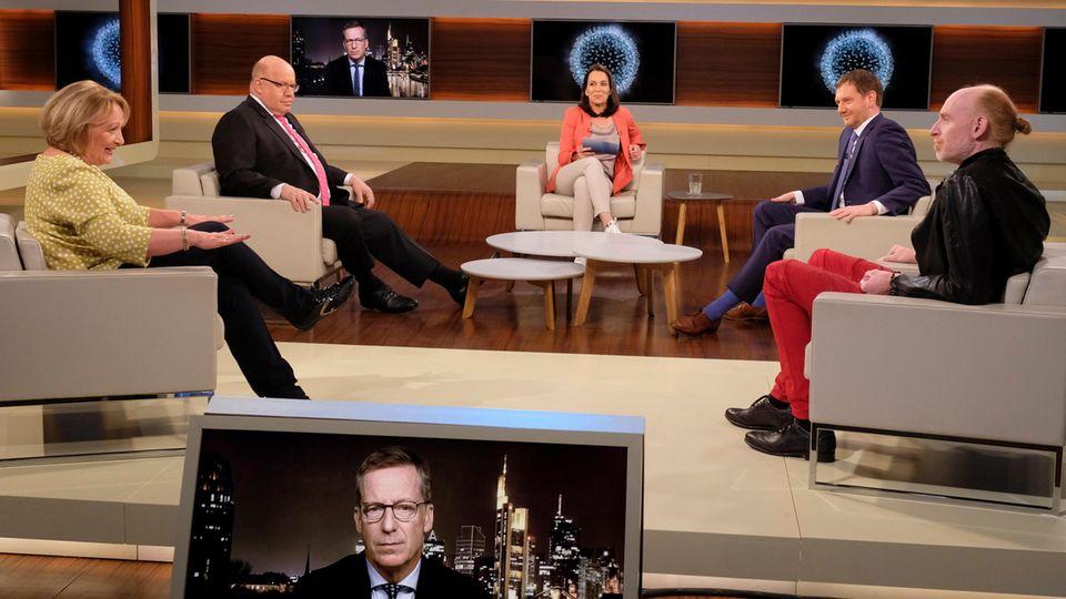 Anne Will (M.) diskutiert in ihrer Talkshow mit ihren Gästen über die Coronakrise in Deutschland
