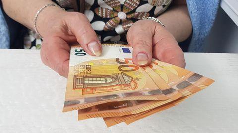 Frau mit 50-Euro-Scheinen in der Hand