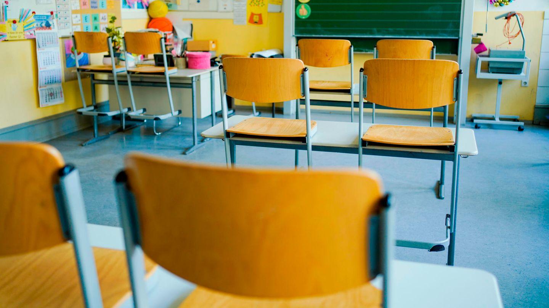 Leerer Klassenraum mit hochgestellten Stühlen