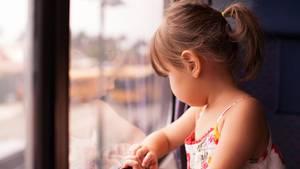 Ein kleines Mädchen guckt aus dem Fenster