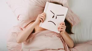 Frau liegt im Bett und hält ein Buch vor ihr Gesicht, auf dem sie ein wütend schauendes Smiley gemalt hat