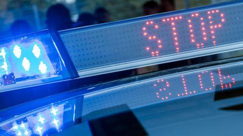 """Der Schriftzug """"Stop"""" ist auf der digitalen Anzeigenleiste auf dem Dach eines Funkstreifenwagens neben dem Blaulicht zu sehen"""