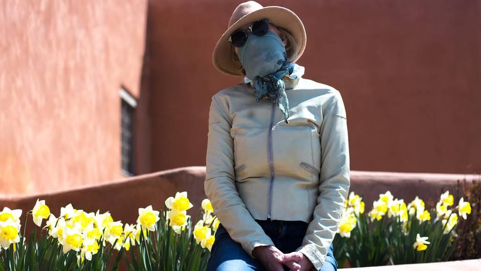 Eine Frau mit Schutzmaske und Sonnenbrille
