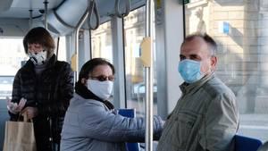 Fahrgäste stehen in einer Straßenbahn und tragen Mundschutz