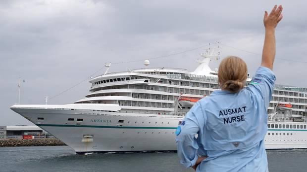 Eine Mitarbeiterin des Australian Medical Assistance Teams (AUSMAT), die mit den Passagieren und der Besatzung des Kreuzfahrtschiffes MV Artania gearbeitet haben, winktzum Abschied, als das Schiff den Hafen von Fremantle verlässt.
