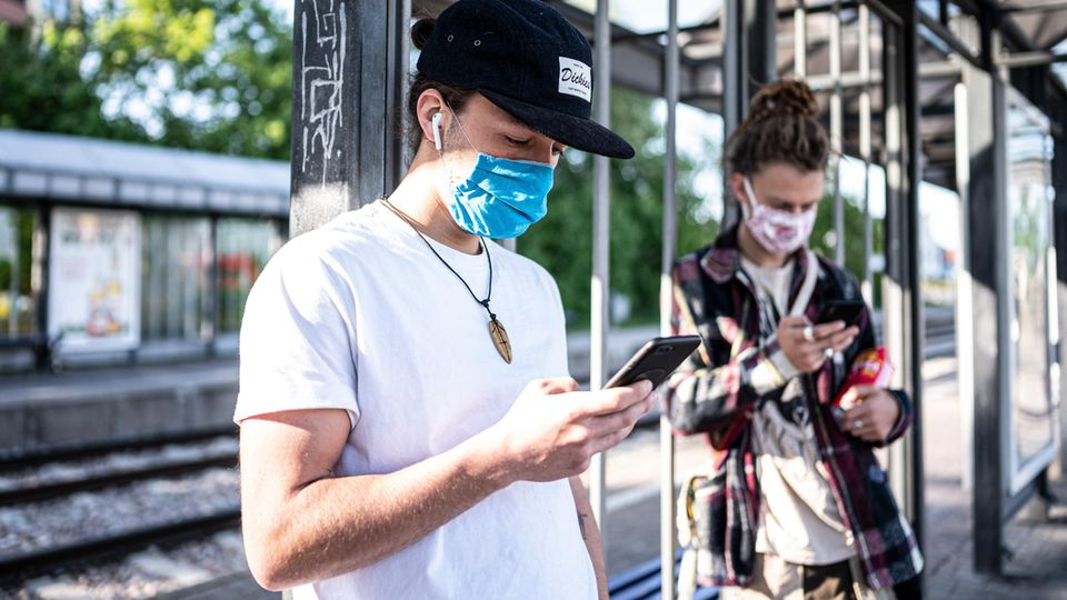 Zwei Personen mit Mundschutz am Handy