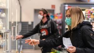 Sachsen, Dresden: Kunden gehen in einem Supermarkt einkaufen und tragen dabei Mundschutz
