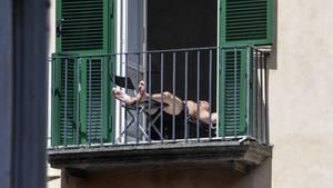Ein Mann sonnt sich auf einem Balkon in Neapel. Seine Füße ragen durch das Gitter.