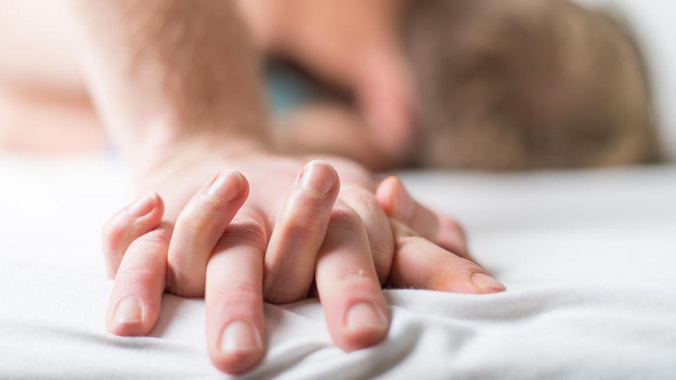 Ein junges Paar liegt im Bett