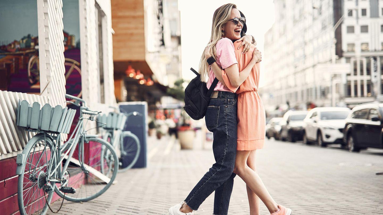 Zwei Frauen umarmen sich auf der Straße