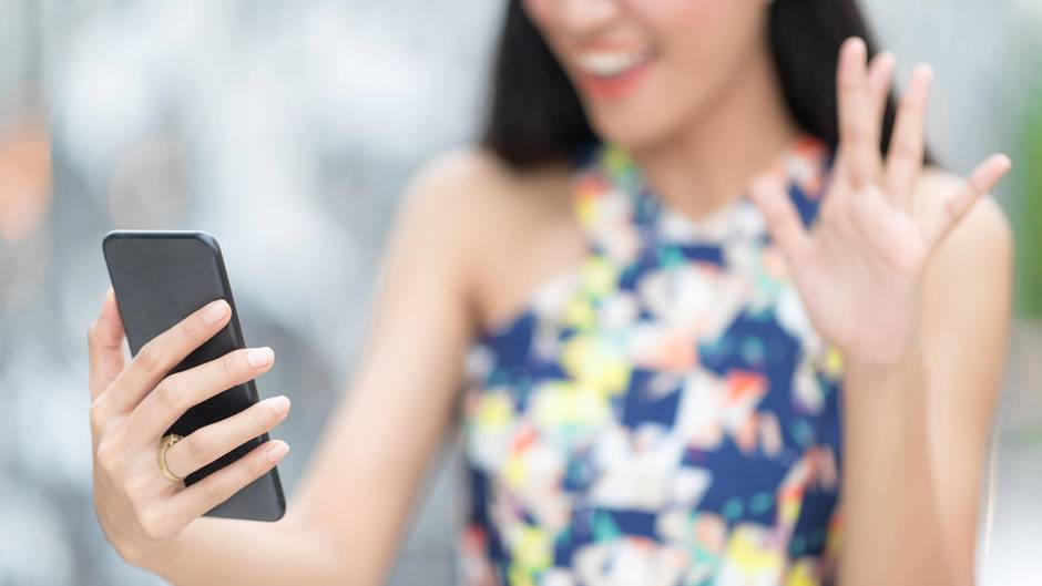Eine Frau winkt in ihr Handy