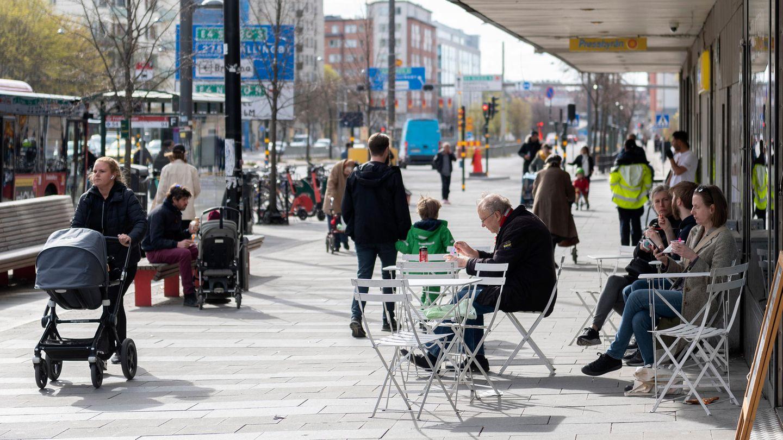 Menschen sitzen im Stadtzentrum von Stockholm vor einem Eiscafé
