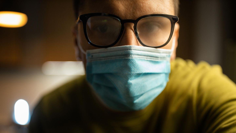 Ein Mann mit gelben Pulli trägt einen blauen medizinischen Mundschutz. Seine Brille ist beschlagen