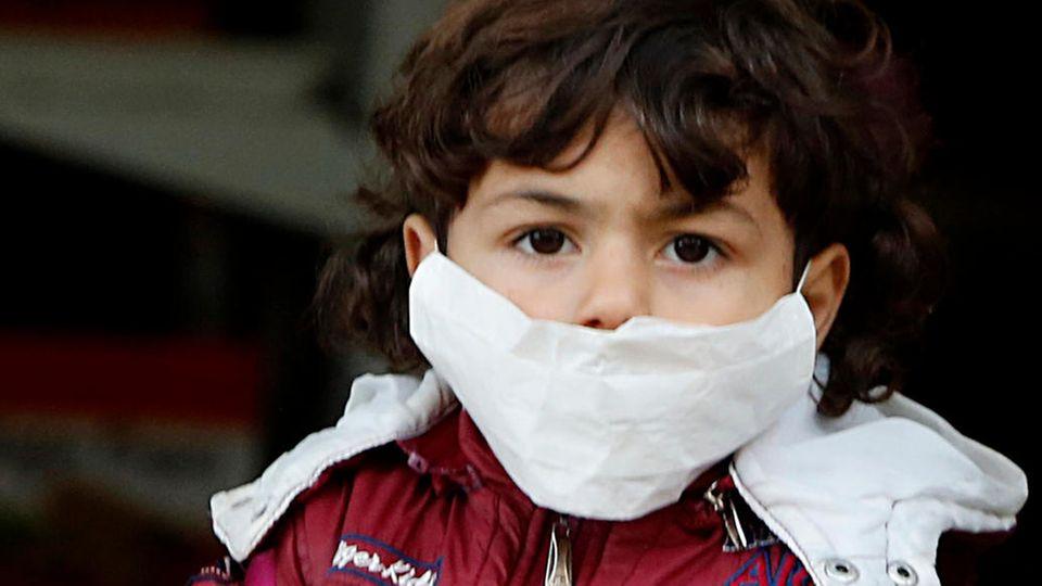 Coronavirus: Ein Kind trägt eine Atemschutzmaske
