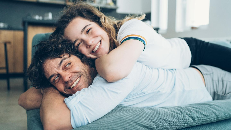 Vater und Tochter liegen auf dem Sofa