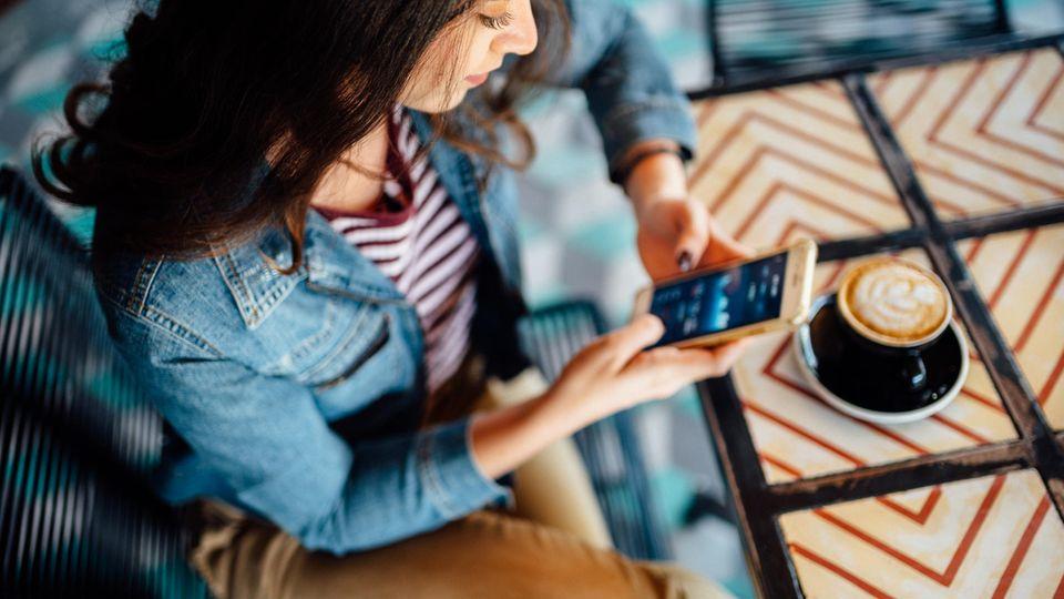Frau sitzt mit Handy in der Hand und einer Kaffeetasse an einem Tisch
