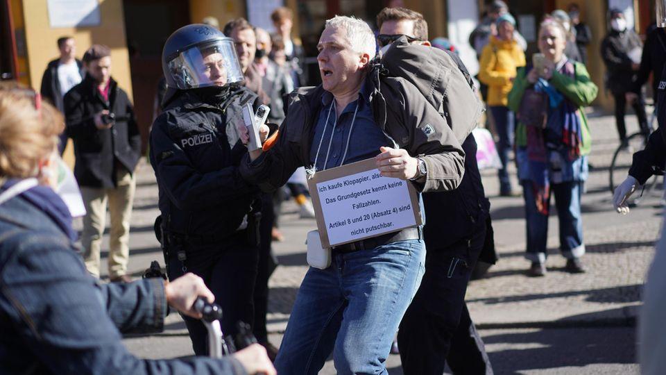 Ein Demonstrationsteilnehmer wird bei einer Demonstration auf dem Rosa-Luxemburg-Platz von Polizisten abgeführt