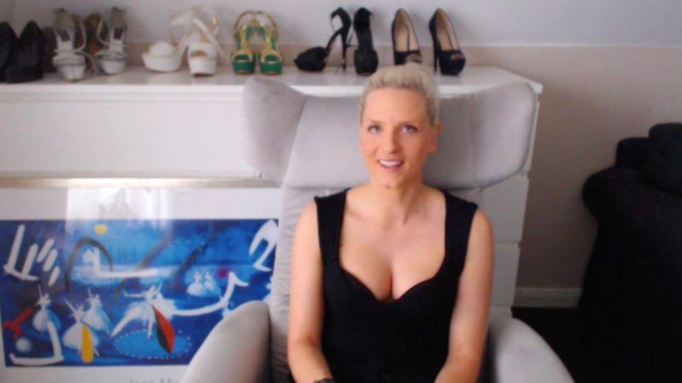 Eine blonde hunge Frau sitzt in schwarzem Top in einem hellgrauen Sessel und lächelt
