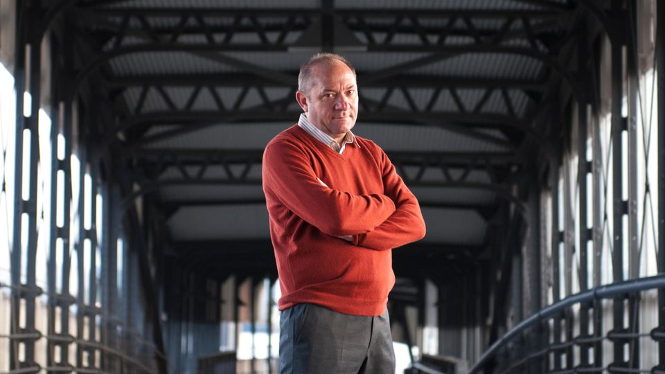 Andreas Heinecke steht mit verschränkten Armen auf einer Hamburger Brücke