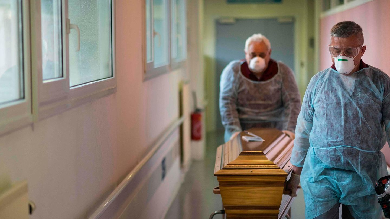 Bestatter in Schutzkleidung im französischen Mulhousetransportieren in einem Sarg einen Corona-Toten