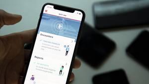 Eine linke Hand hält ein Smartphone, auf dessen Display der Startbildschirm der schweizer Corona-App leuchtet