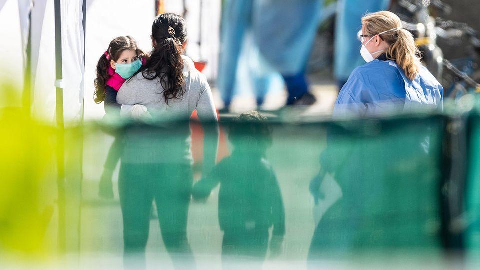 Eine Frau in einem Schutzanzug begleitet eine Fau mit zwei Kindern aus einem Wohnkomplexes zu einem Corona-Test
