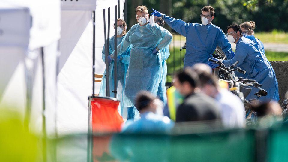 Mitarbeiter vom Gesundheitsamt warten an den Zelten, vor einem Wohnkomplex, darauf, Corona-Tests durchzuführen