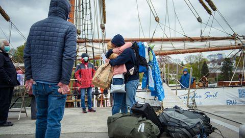 Mutter und Tochter umarmen sich zur Begrüßung. Im Hintergrund ist ein hölzerner Mast eines Segelschiffs zu sehen