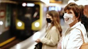 Frau mit Mundschutzmaske mit aufgedrucktem lächelndem Mund