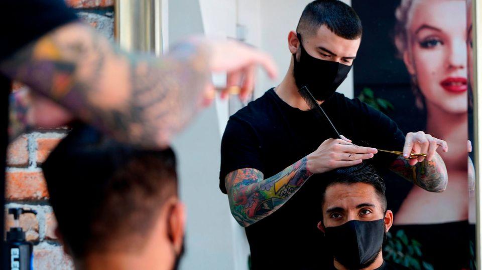 Friseur schneidet einem Kuden die Haare - beide tragen eine Mundschutzmaske