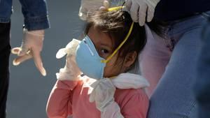 Einem Mädchen, das zu große Latexhandschuhe trägt, wird eine Gesichtsmaske für Erwachsene aufgesetzt