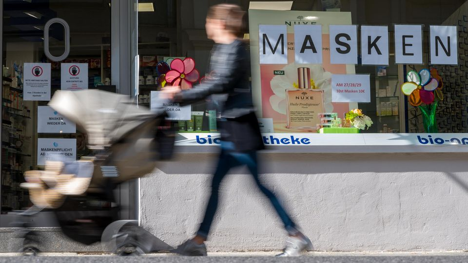 Eine Frau schiebt einen Kinderwagen an einer Apotheke vorbei, die Mundschutzmasken anbietet