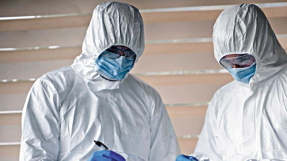 In Schutzkleidung gehüllte Ärzte