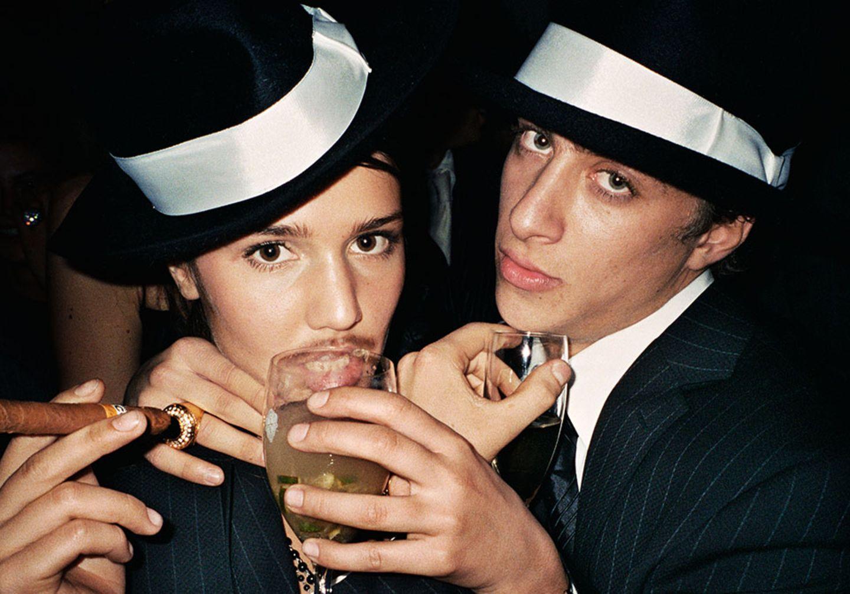 Eine Frau und ein Mann posieren in Nadelstreifenanzügen mit Hüten, Weingläsern und Zigarre