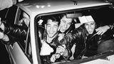 Junge Männer sitzen im Auto und strahlen