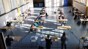 Schüler mit Mundschutz sitzen bei der Prüfungsvorbereitung fürs Abitur in einer zum Schulraum umfunktionierten Turnhalle