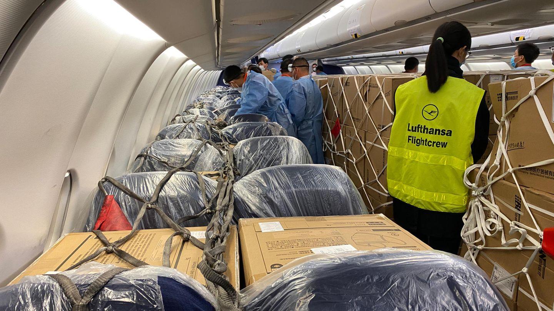 Beim Beladen der Sessel in der Business Class einer A330:Eine Mitarbeiterin einer Lufthansa Flight Crew überprüft, ob die Fracht fest verzurrt ist.