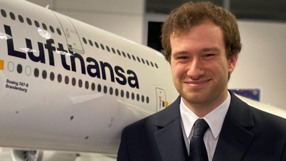 FlugbegleiterAndreas Rückle neben einem Modell einer Boeing 747-8