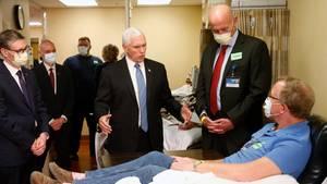 Um einen Mann auf einer Krankenhausliege stehen Anzugträger und Pflegepersonal mit Atemmasken - bis auf einen weißhaarigen Mann