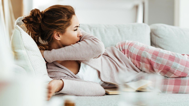 Impfung Pneumokokken: Eine Frau liegt auf dem Sofa und hustet