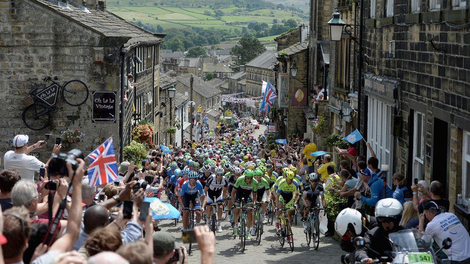 Tour de France: Das Peloton der Tour zwängt sich durch eine enge Gasse