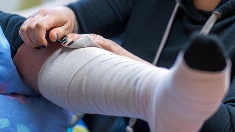 Eine Frau legt einer zu pflegende Person einen Thrombose-Verband an