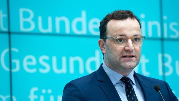 Bundesgesundheitsminister Jens Spahn steht vor einer türkisen Wand mit den Schriftzug seines Ministeriums und spricht ins Mikro